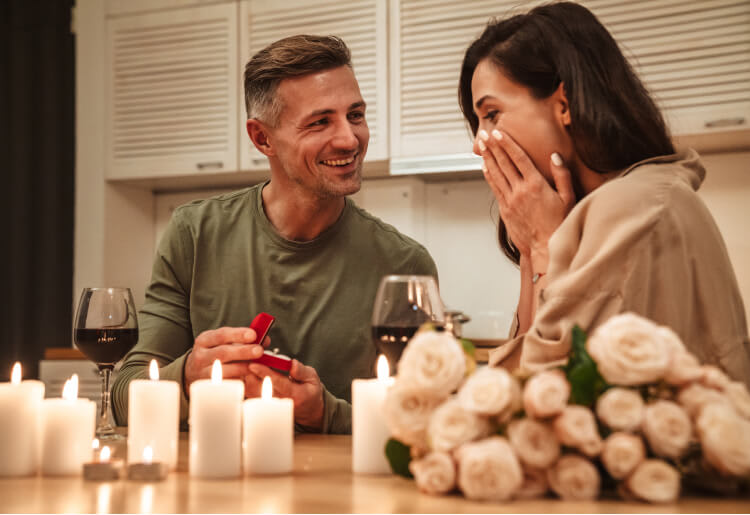 Good looking man proposes to his girlfriend with a ring