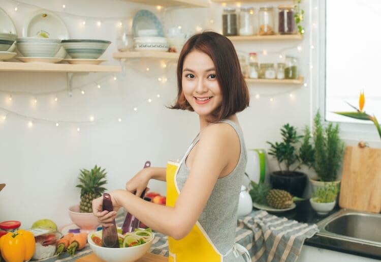 Single woman cooking in kitchen