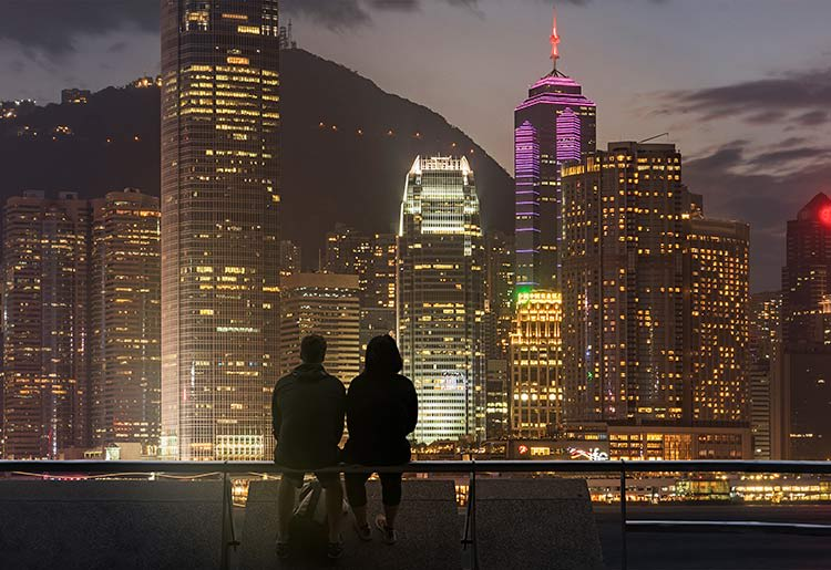 A silhouette of a couple in front of the skyline of a major city