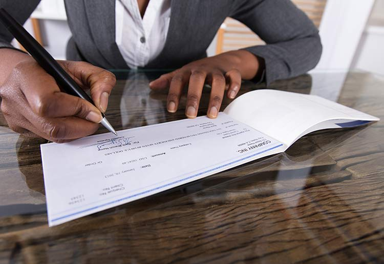 Woman signing business check
