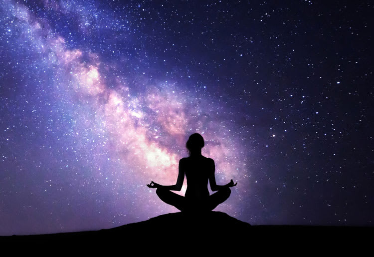 A woman meditates against a view of the milky way at night