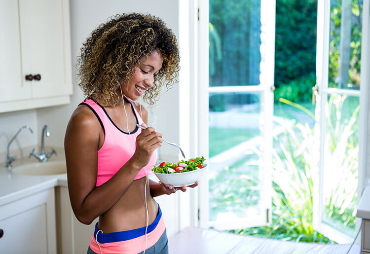 Fit African-American woman eating a salad