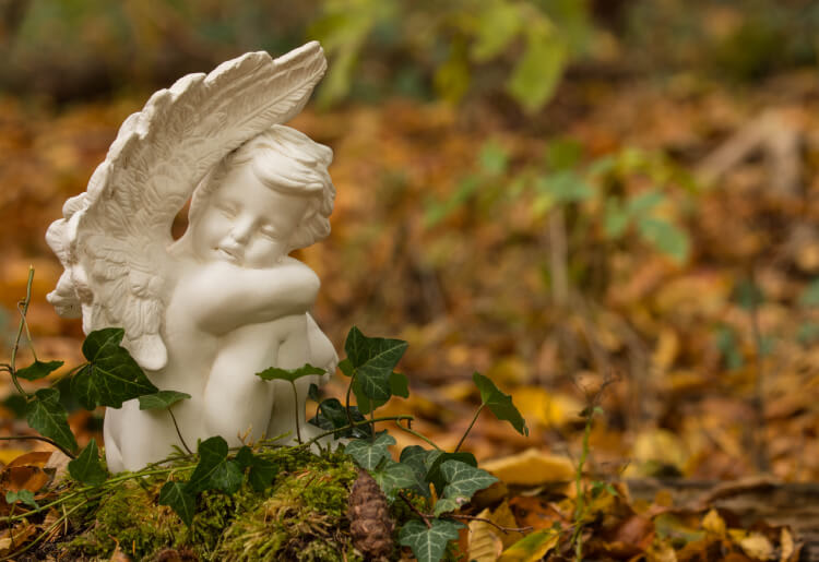 An angel statue sits on the ground in the forest