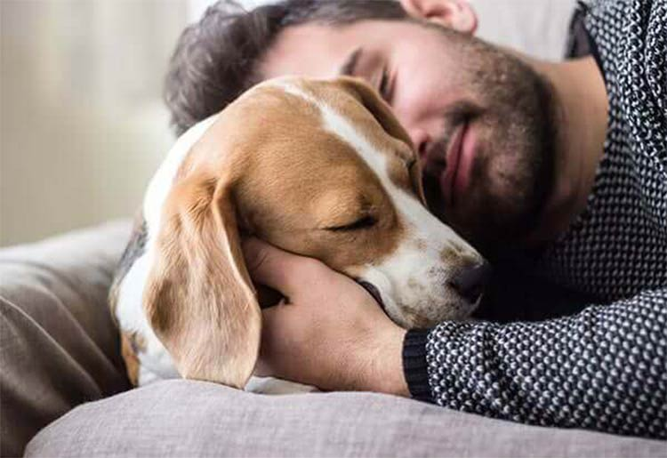 Man snuggling his dog