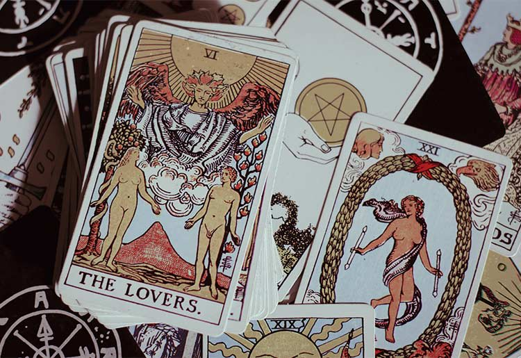 """A tarot deck lies on a table showing the """"The Lovers"""" card"""