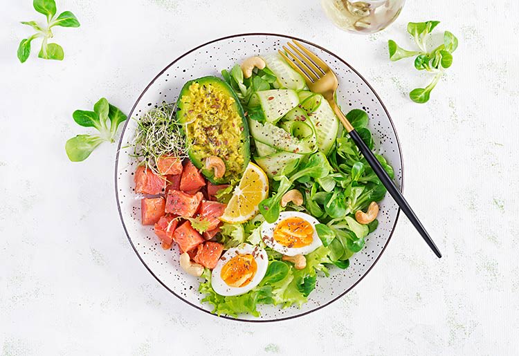 A healthy bowl of salad with avocado, eggs, and tomato.