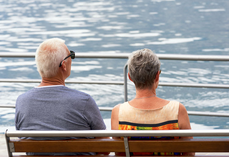 An elderly couple with hearing aids enjoys the summer on a bench near the water